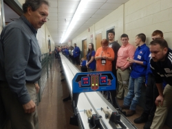 Dr. Field (far left) helps TSA students with the dragster competition